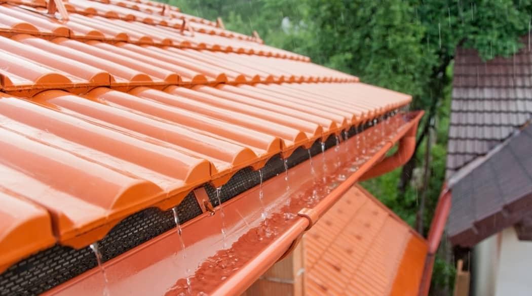 Dachentwässerung: roten Ziegeln und eine Dachrinne, in die Regenwasser fließt