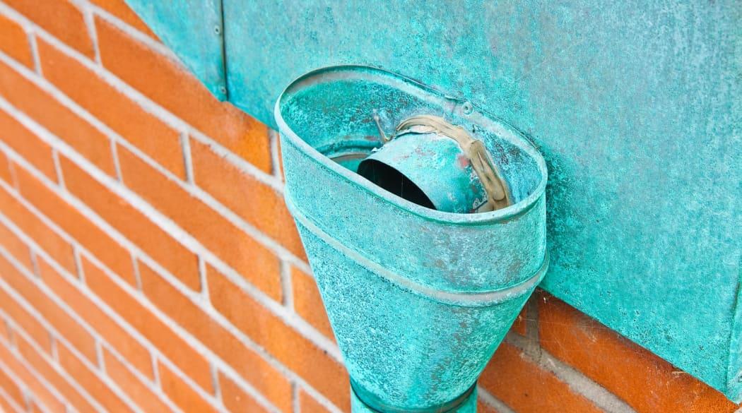 Dachentwässerung: ein Rinnenkessel aus Kupfer mit grüner Patina