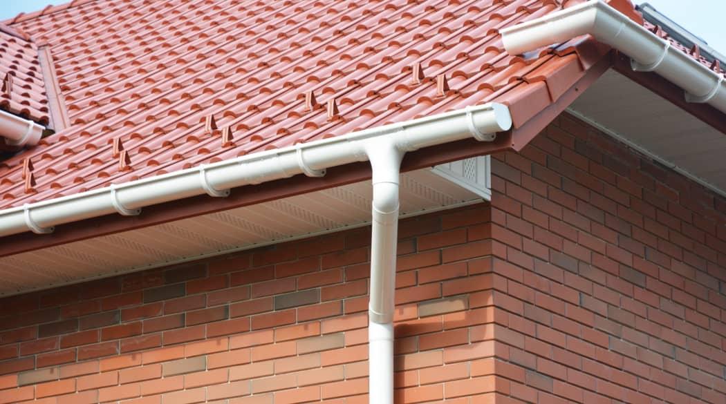 Dachentwässerung: eine Dachrinne aus weißem Kunststoff