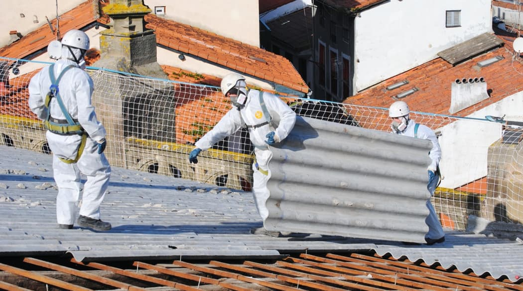Drei Handwerker entfernen Asbestplatten
