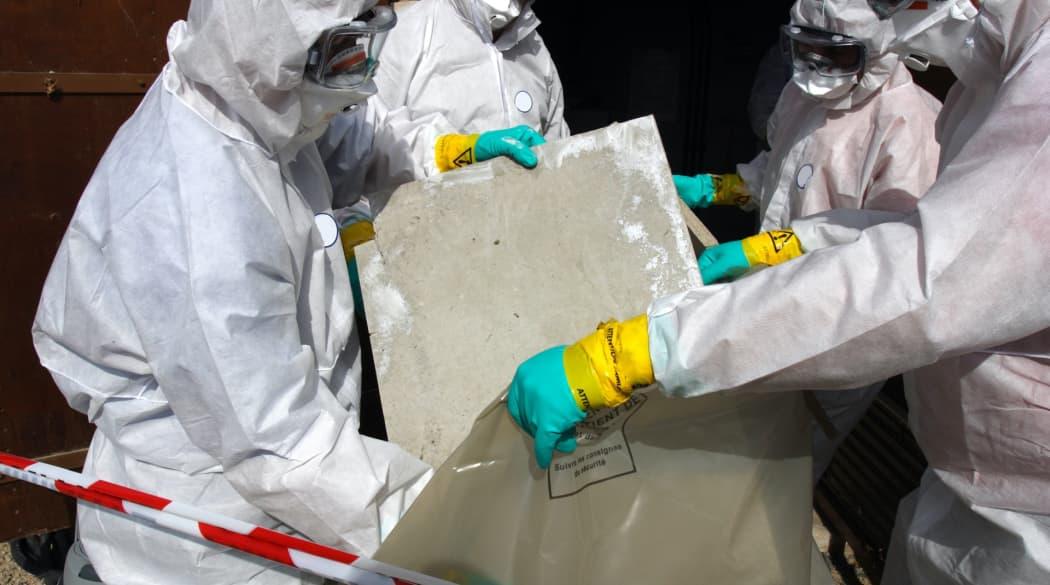 Handwerker entfernen alte Asbestplatten