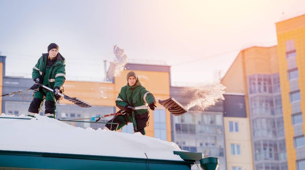 Schneelast auf dem Dach: zwei Männer räumen mit Schneeschaufeln Schnee vom Dach