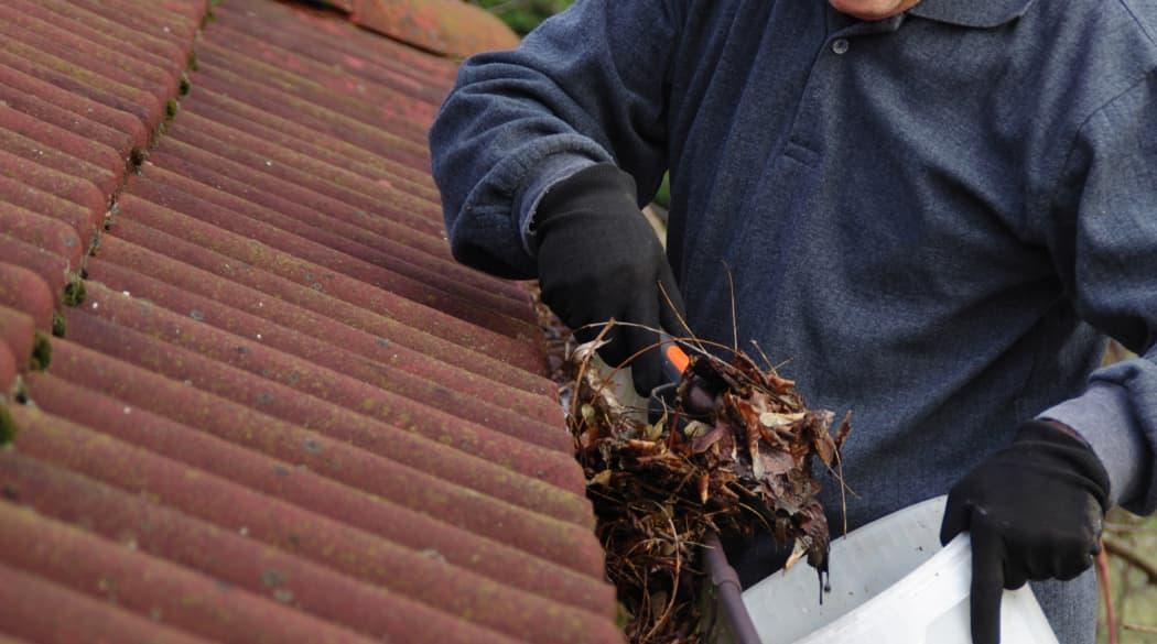 Dachwartung: ein Mann reinigt die Dachrinne von Laub und Schmutz